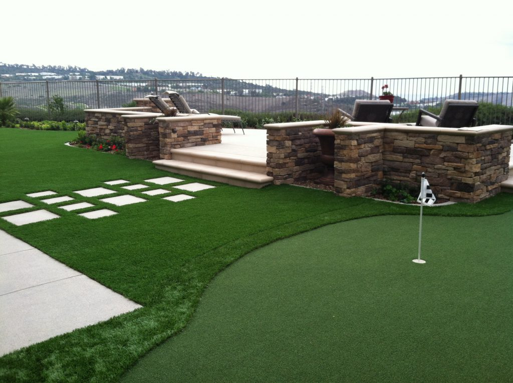 Putting green in backyard overlooking a range of foot hills.