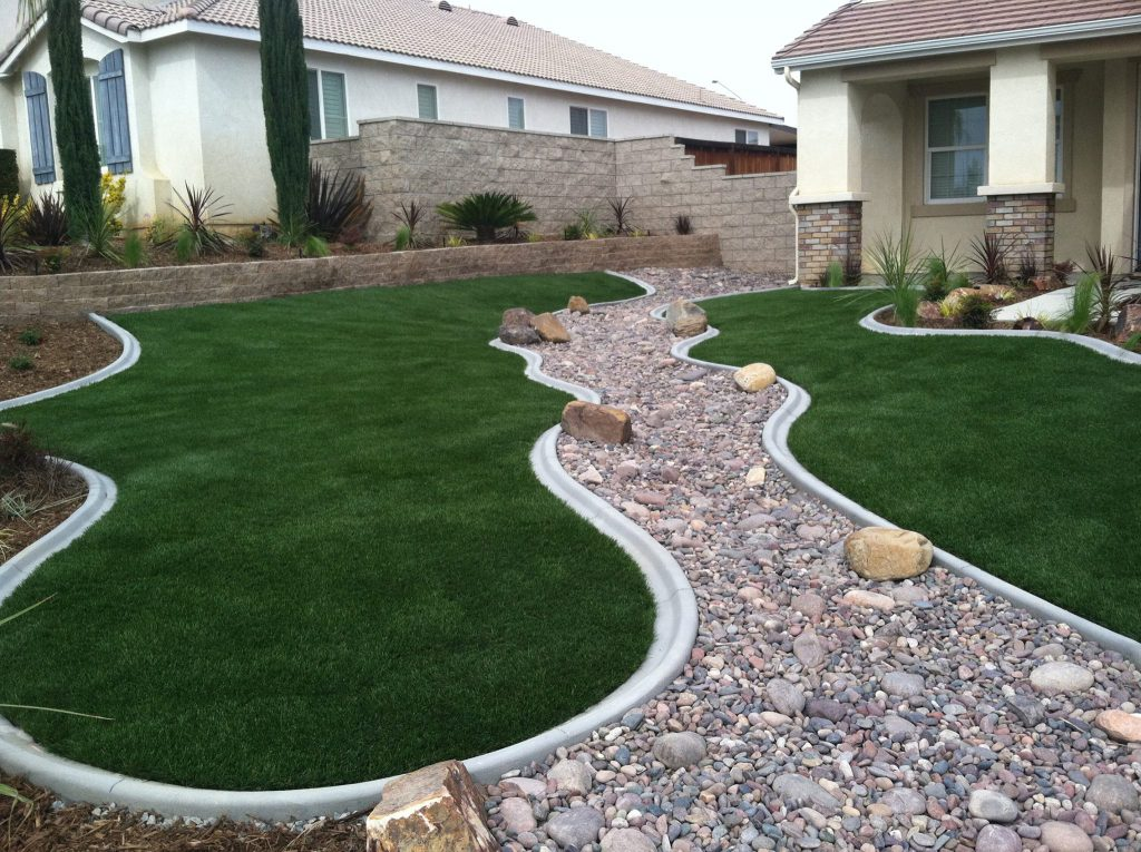 Artificial grass smoothly running along the wavy edge of a gravel path