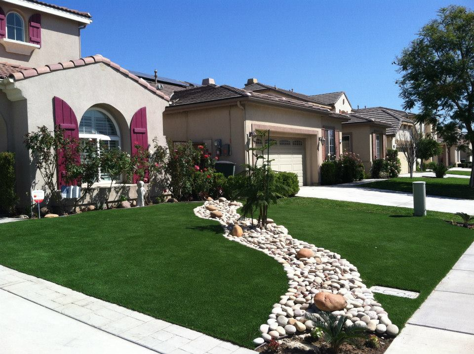 Two areas of artificial grass around a winding granite path