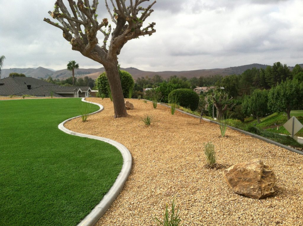 Artificial grass lawn cut perfectly along a winding edge