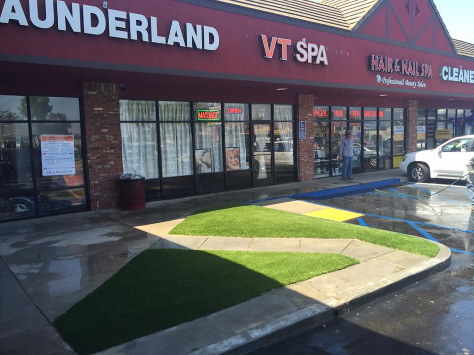 Artificial grass filling in a sidewalk outside of a block of stores