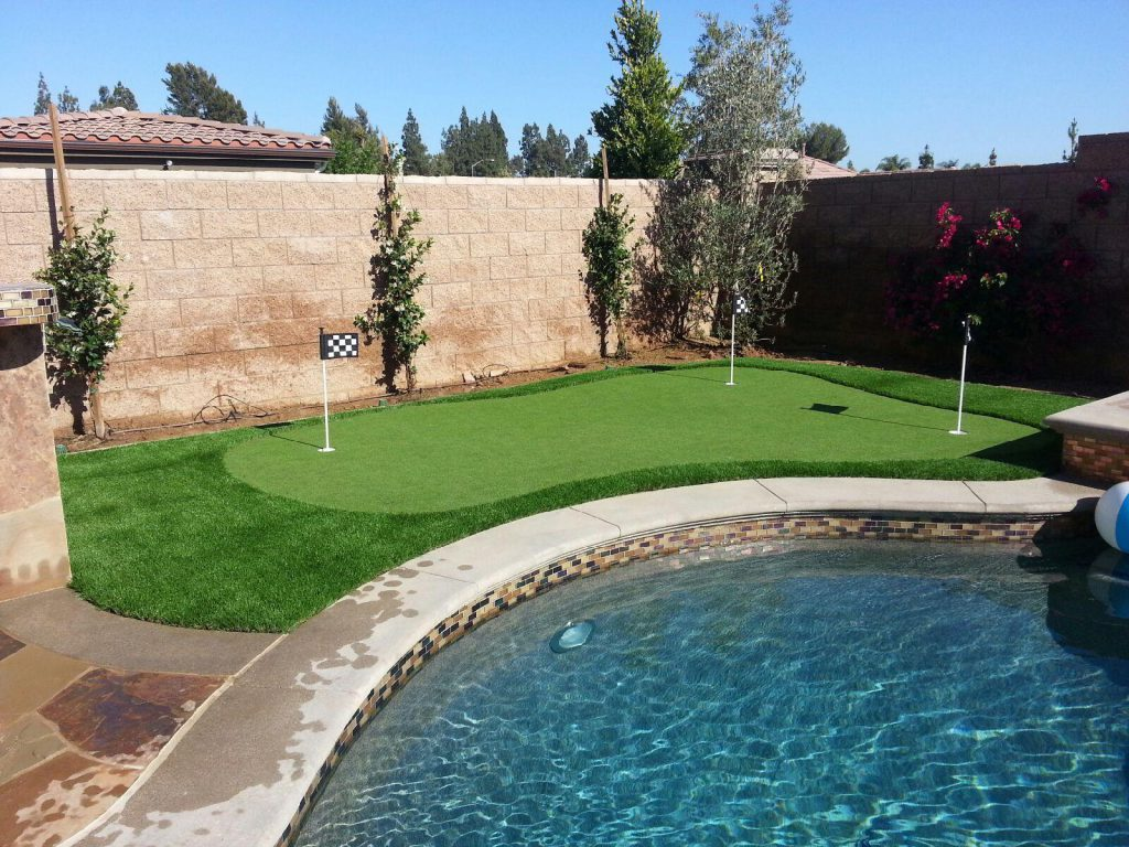Artificial grass and a putting green next to a pool in a backyard