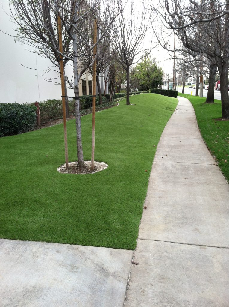 Artificial grass filling the exterior of a sidewalk intersection