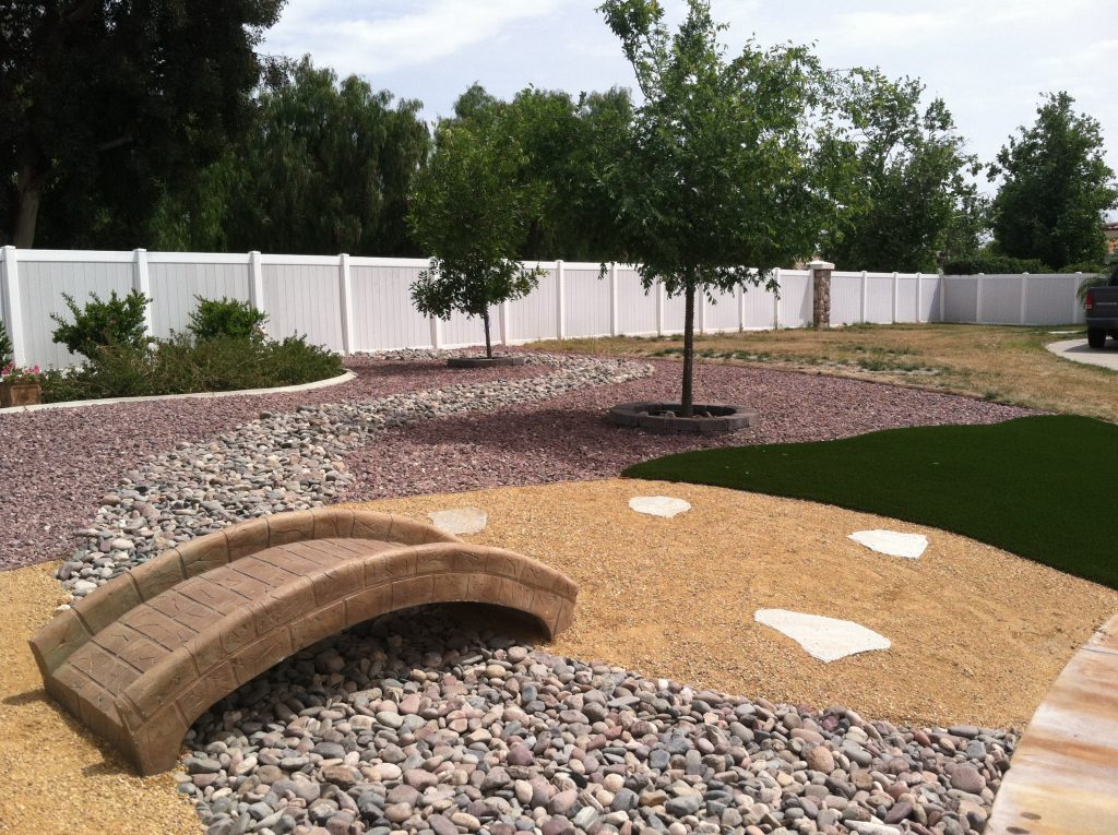 Big backyard with a large selection of different materials including granite, gravel, sand, and artificial grass