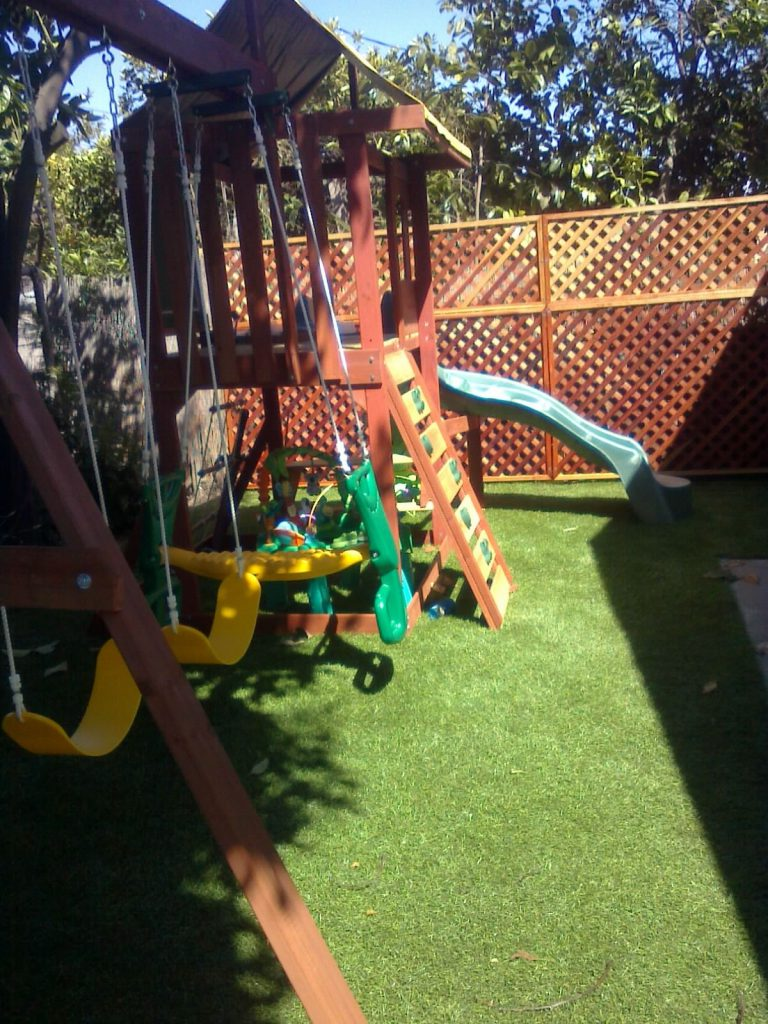 Playground in a backyard on top of artificial grass