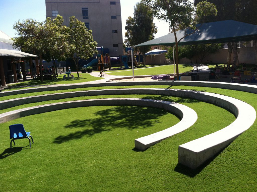 An outdoor auditorium for a school with artificial grass filling in the gaps between concrete semi-circles