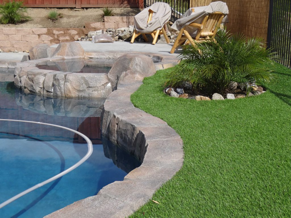 Artificial grass alongside a wavy curved edge of an outdoor pool